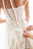 Atar el vestido de las novias Fotos de archivo libres de regalías
