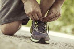 Atar el zapato de los deportes en el camino Imagen de archivo