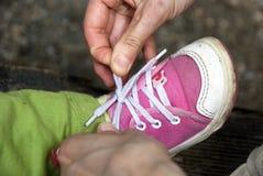 Atar los zapatos de bebé Imágenes de archivo libres de regalías