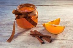 Atasco anaranjado en el tarro de cristal y pedazos de naranja en la tabla de madera, franco fotografía de archivo libre de regalías