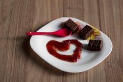 Atasco de frambuesa, caramelos dulces y cuchara del rojo del té imagenes de archivo