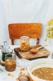 Atasco de frambuesas Mano femenina que hace el atasco, en una tabla blanca rústica Imagen de archivo libre de regalías