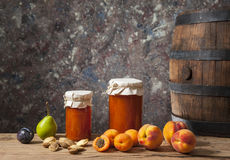 Atasco del albaricoque, fruta fresca y un barril de madera Fotografía de archivo