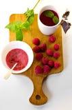 Atasco del té y de frambuesa, menta y frambuesas frescas Imagenes de archivo