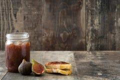 Atasco dulce del higo en tarro en la tabla de madera Imagen de archivo