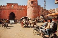 Atasco en el camino de tierra de la ciudad india con las puertas antiguas del ladrillo Foto de archivo libre de regalías