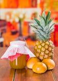 Atasco hecho en casa de la piña con la fruta fresca y poco pan en una tabla de madera Imagen de archivo