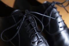 Ate el detalle del primer de un par de zapatos de cuero negros clásicos Foto de archivo libre de regalías