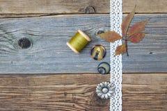 Ate la cinta, botones del vintage, carretes del hilo y seque las hojas Imagenes de archivo