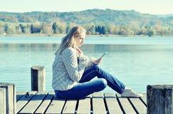从ateblet的女孩读书 免版税图库摄影