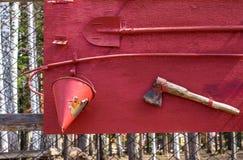 Ateie fogo ao protetor com uma pá, cubetas, machado na cerca que cerca o objeto da natureza foto de stock