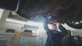 Atelier automatique mécanique - un mécanicien vérifie la suspension de la voiture, grande-angulaire Photos stock
