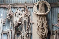 Atelier avec l'affichage de l'équipement, des cordes et des outils de ferme de la poussière accrochés contre un mur de fer ond images stock