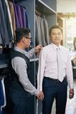 Atelier client. Mature Vietnamese men at atelier ordering a suit royalty free stock photography