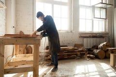 Atelier de menuiserie L'homme à l'aide de la main électrique a vu sur les planches en bois Images libres de droits