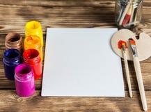 Atelier du `s d'artiste Vue supérieure de palette de pinceaux et de peintures acryliques avec la toile blanche Ensemble de brosse Photo libre de droits
