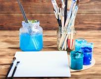 Atelier du `s d'artiste Vue supérieure de palette de pinceaux et de peintures acryliques avec la toile blanche Ensemble de brosse Image stock