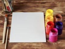 Atelier du `s d'artiste Vue supérieure de palette de pinceaux et de peintures acryliques avec la toile blanche Ensemble de brosse Photographie stock