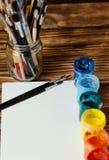 Atelier du `s d'artiste Vue supérieure de palette de pinceaux et de peintures acryliques avec la toile blanche Ensemble de brosse Photos stock