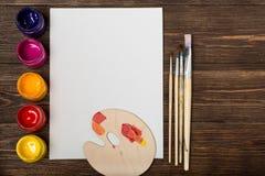 Atelier du `s d'artiste Vue supérieure de palette de pinceaux et de peintures acryliques avec la toile blanche Ensemble de brosse Images stock