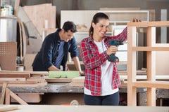 Atelier femelle de Drilling Wood In de charpentier Images stock