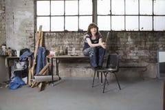 Atelier femelle de With Paintbrush In d'artiste Photo stock