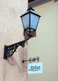 Atelier and lamp. Old metallic lantern and board sign Royalty Free Stock Photography
