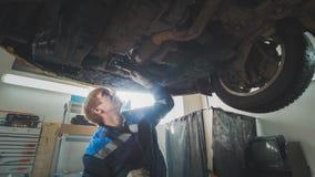 Atelier mécanique - un mécanicien vérifie la suspension de la voiture, grande-angulaire Photo libre de droits