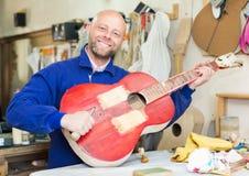 Atelier posing with his guitars. Happy atelier posing with his guitars at workshop Royalty Free Stock Photo
