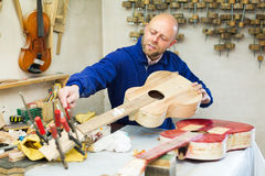 Atelier posing with his guitars. At workshop Stock Images
