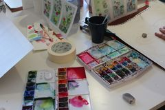 Atelier still life - aquarelle colours, brushes, empty mug and other objects. Relax with art therapy - preparation for aquarelle painting royalty free stock images