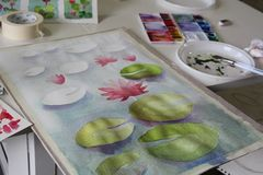 Atelier still life - a painting of water lilies in progress, aquarelle colours, brushes and other objects. Relax with art therapy - preparation for aquarelle stock images