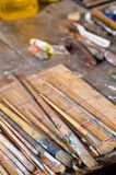Atelier table. Messy atelier table with many paintbrushes and other stuff royalty free stock photography