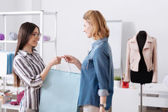 Atelier workers holding a bag together. Colleagues bond. Pleasant cheerful women standing at the atelier room, holding together a big blue bag while having a Royalty Free Stock Images