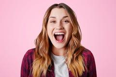 Atelieraufnahme der überglücklichen glücklichen Frau lacht über guten Witz, hält Mund weit geöffnet und ist aufgeregt, lokalisier stockfotos
