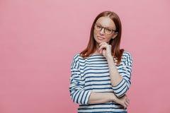 Atelieraufnahme der attraktiven Frau mit dem braunen Haar, Kreuze überreichen Kasten, hält Hand unter dem Kinn, fokussiert mit na lizenzfreie stockfotos