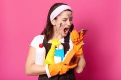 Atelieraufnahme der Frau mit den Putzmitteln, die in der Hand Telefon halten, auf Schirm schauen und schreien, hat und verärgert  stockbild