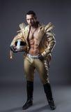 Atelieraufnahme des heißen muskulösen Mannes im goldenen Kostüm stockfotos