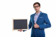 Atelieraufnahme des jungen hübschen Geschäftsmannes, der leeres blackboa hält stockbild