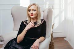 Atelieraufnahme des jungen und schönen Mädchens, das im schwarzen Kleid trägt im Studio sitzt Blondes Mädchen Lizenzfreies Stockbild