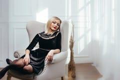 Atelieraufnahme des jungen und schönen Mädchens, das im schwarzen Kleid trägt im Studio sitzt Blondes Mädchen Stockfotos
