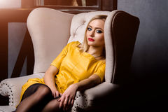 Atelieraufnahme des jungen und schönen Mädchens, das im Stuhl im gelben ledernen Kleid trägt im Studio sitzt Blondes Mädchen Lizenzfreies Stockfoto