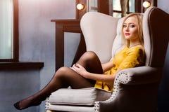 Atelieraufnahme des jungen und schönen Mädchens, das im Stuhl im gelben ledernen Kleid trägt im Studio sitzt Blondes Mädchen Stockfoto