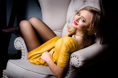Atelieraufnahme des jungen und schönen Mädchens, das im Stuhl im gelben ledernen Kleid trägt im Studio sitzt Blondes Mädchen Lizenzfreie Stockfotos