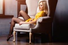 Atelieraufnahme des jungen und schönen Mädchens, das im Stuhl im gelben ledernen Kleid trägt im Studio sitzt Blondes Mädchen Stockfotos