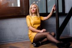Atelieraufnahme des jungen und schönen Mädchens, das nahe Fenster im gelben ledernen Kleid trägt im Studio sitzt Blondes Mädchen Stockfotos