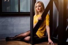 Atelieraufnahme des jungen und schönen Mädchens, das nahe Fenster im gelben ledernen Kleid trägt im Studio sitzt Blondes Mädchen Lizenzfreie Stockfotos