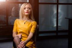 Atelieraufnahme des jungen und schönen Mädchens, das nahe Fenster im gelben ledernen Kleid trägt im Studio sitzt Blondes Mädchen Stockfoto