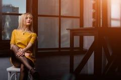 Atelieraufnahme des jungen und schönen Mädchens, das nahe Fenster im gelben ledernen Kleid trägt im Studio sitzt Blondes Mädchen Stockbild