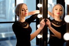 Atelieraufnahme des jungen und schönen Mädchens, das nahen Spiegel im schwarzen Kleid trägt im Studio steht Blondes Mädchen Lizenzfreie Stockfotos